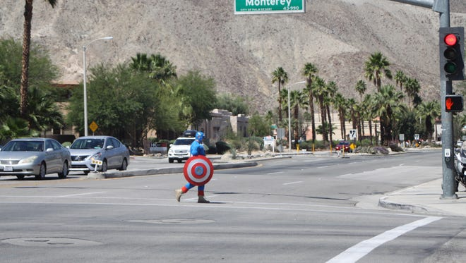 Riverside County Sheriff's Deputy Steven Nelson crosses Monterey Avenue in Palm Desert while dressed as Captain America. He was participating in a pedestrian safety enforcement operation.