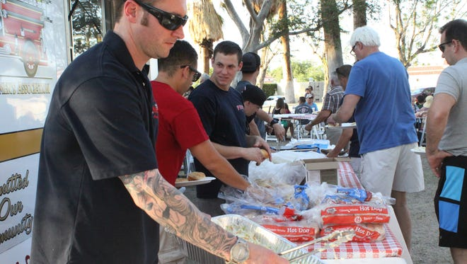 Firefighters serve fish, corn, cole slaw, hamburgers and other goodies at the Palm Springs Firemen's Association Fish Fry Saturday, June 4, 2016.