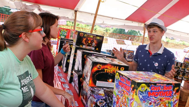 Will Silvers explains the different fireworks that are available to Ariana Desrosier, left, and Kimberly Rosenbaum at Fireworks Supermarket, located next to Dollar General Store on Tiny Town Road last 4th of July season.