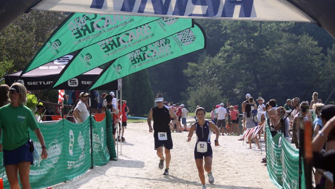 Runner cross the finish line at a past Lake Lure Triathlon. The 12th annual race, part of the Lake Lure Olympiad, is Aug. 13.