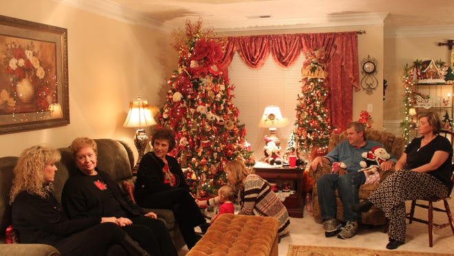 Cindy Shirley (left) spends time with members of her family in her home, which she has filled with 36 fully decorated Christmas trees.