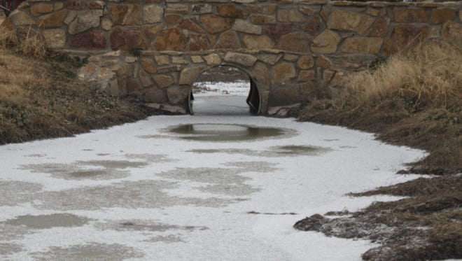 A small creek is frozen and coated with a thin layer of snow Friday near the Pecos River.
