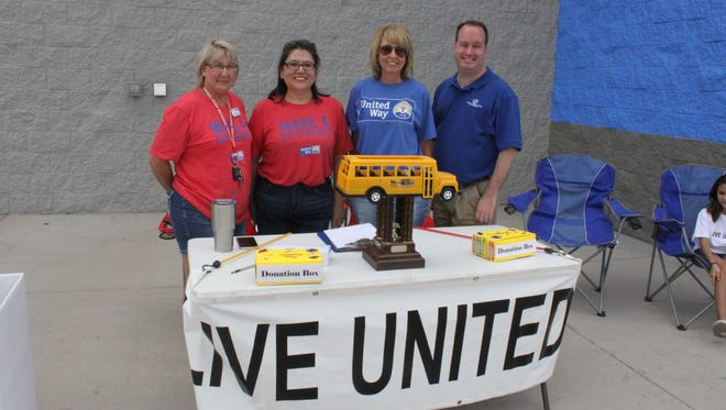 United Way and Boy and Girls Club volunteers collect donations for the annual Stuff the Bus event, Friday at Walmart.