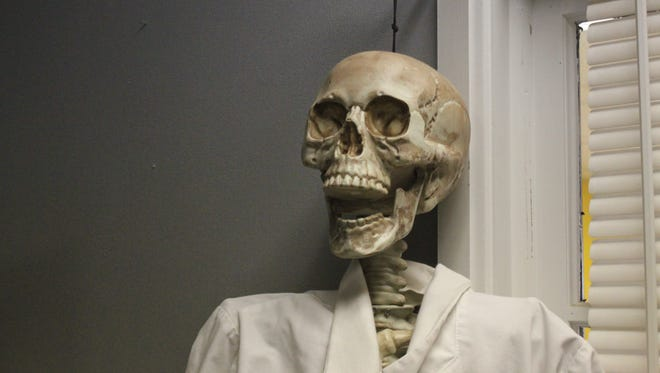 A skeleton stands frightfully at Entrapment Escape Rooms.
