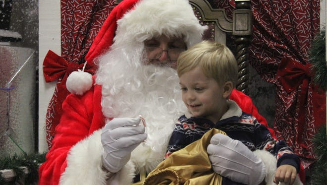 Lucas Sullivan, 2, inspects a candy cane offered to him by Santa Claus, Dec. 22 at the Carlsbad Mall.