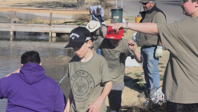 Members of local boy scout troop 212 work together to pick up trash along the Pecos River, March 10, 2018 at the Lower Tansil Dam.