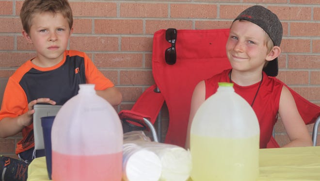 Danny and Nathan Taylor offer up glasses of ice-cold lemonade, June 20, 2018 outside Dollar General on Pierce Street.
