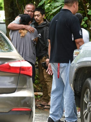 A man find comfort in a hug near a Chalan Koda residence where Guam Police Department personnel conduct a death investigation in Dededo on Saturday, June 16, 2018. Limited information is available until an autopsy, schedule to be done later this week, is performed by the island's chief medical examiner, said Sgt. Paul Tapao, GPD spokeman.