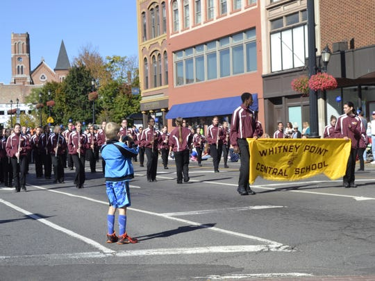 A young spectator snaps a photo of Whitney Point's marching band at Monday's Mirabito Columbus Day Tournament of Bands Parade in Binghamton.