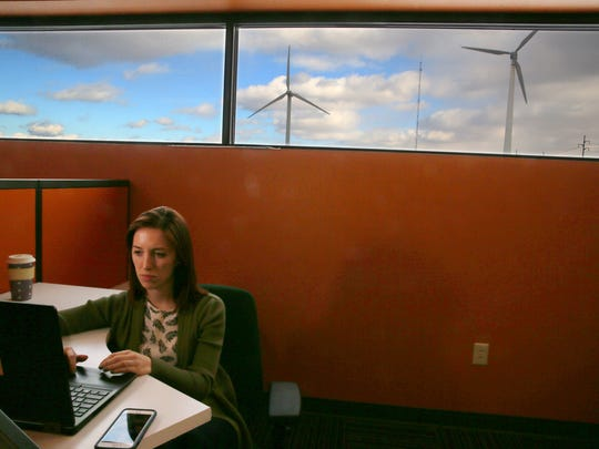 Kathleen Connolly, PV design manager, works on a project at her desk as giant wind turbines rotate outside the offices at SunCommon.