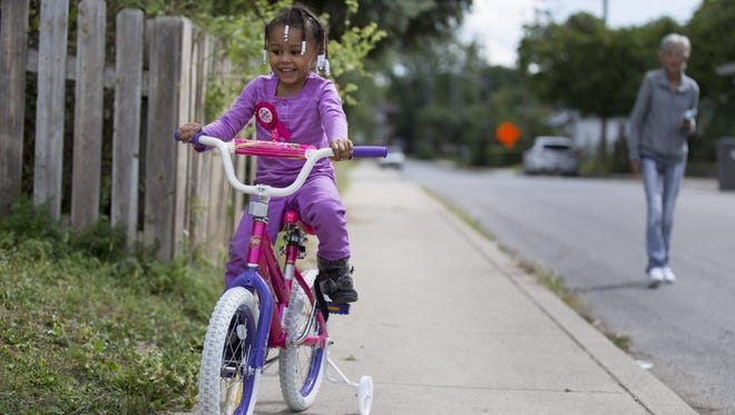 Abrianna Dye, 4, is watched by her great-grandmother, Pat Lippard, on Sept. 13, 2015, as Dye rides her new bicycle down the sidewalk of her family's home on the city's east side.
