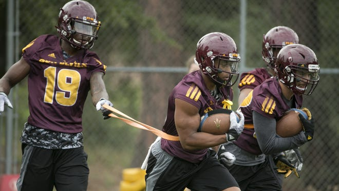 ASU wide receiver Cameron Smith carries the ball as he is held back with a band by wide receiver Ellis Jefferson during ASU football camp practice at Rumsey Park in Payson on Wednesday, August 3, 2016. ASU head to mov their practice from Camp Tontozona to the field at Rumsey Park because the field at Camp Tontozona was too wet from rain.