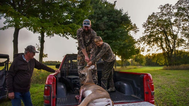 Jonathan and Easton VanMiddlesworth load Easton's first buck on Saturday, Sept. 14, 2019 in Climax. The response to the pandemic may have trimmed the number of hunters in the state's annual firearms season last November.