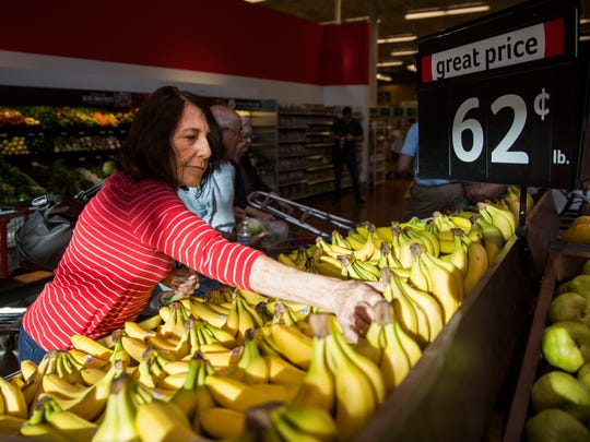 Susana Mildner picks up a bunch of bananas at the Winn-Dixie grand reopening on Wednesday, May 16, 2018.
