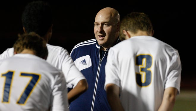 Collegiate co-head coach Chad Wozniak gives instructions to his team against Male during their match at St. X High School.Oct. 13, 2015