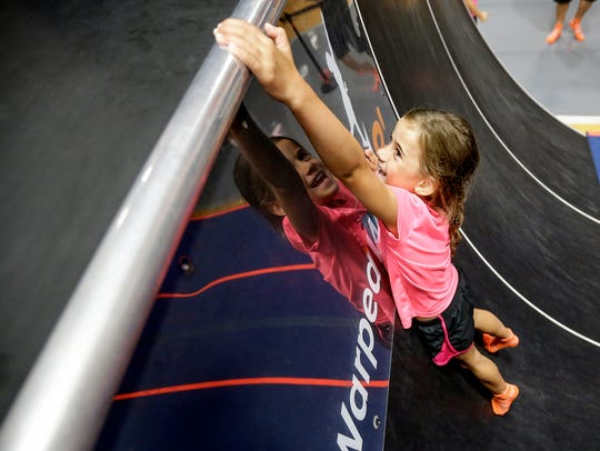 A young girl reaches the top of the warped wall at