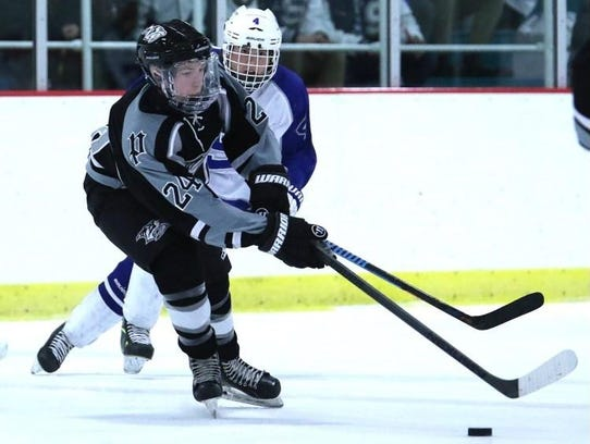 Battling for a loose puck Wednesday at Plymouth Cultural