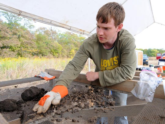 Ryan O'Beirne, an anthropology student at Purdue University, screens soil in 2009 at Strawtown Koteewi Park.