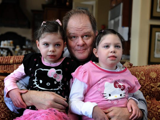 Hugh Hempel poses for this 2012 photograph with his daughters Cassi, left, and Addi, who have Neimen Pick C, a rare childhood Alzheimer's.