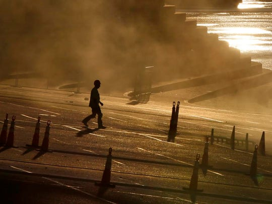 A worker walks along the public landing, where light hits concrete dust on Wednesday morning.
