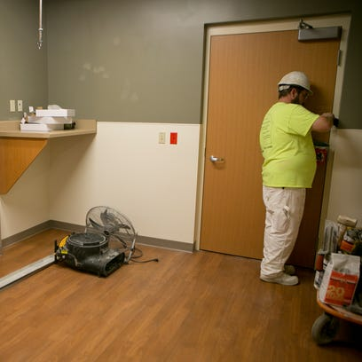 A construction worker paints a door frame in the new