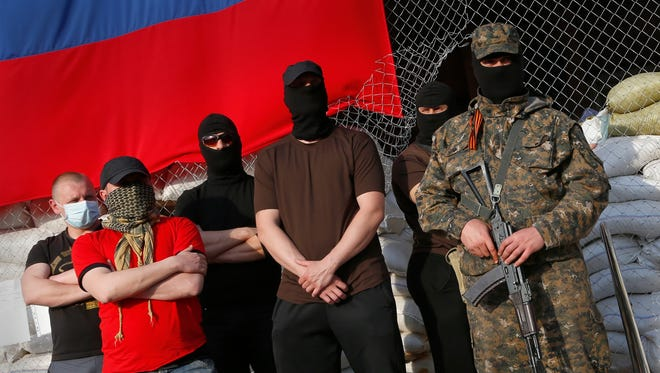 Masked pro-Russia armed men stand at the city hall during negotiations about the release of foreign military observers being held in Slovyansk, eastern Ukraine, on April 27.