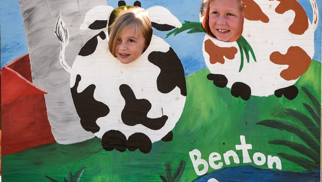Kylie and Macy Konz smile for a photograph behind a background Sunday at the Benton County Fair in Sauk Rapids.