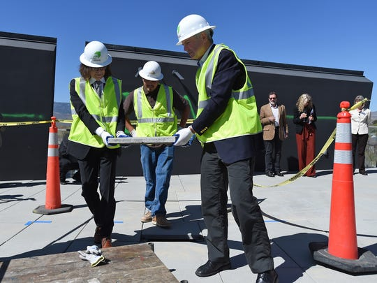 Nevada Museum of Art CEO David Walker, left, and Steven Nightingale remove the first tile from the roof at the Nevada Museum of Art during a press conference announcing the Sky Room. It is a complete renovation of the museum roof and will be available for private events, weddings, retreats, and community activities.