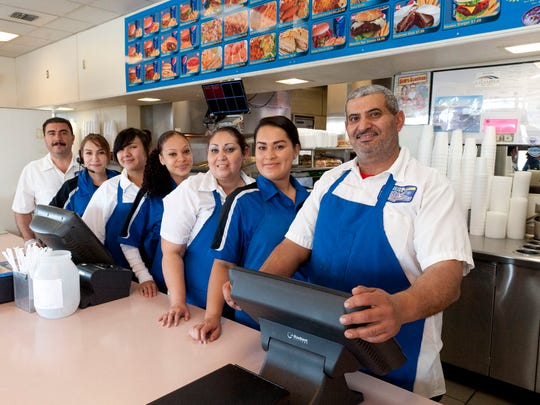 Abdul Saleh, right, owner of Bob's Drive In, and his staff in the new Tulare location on Thursday, March 5, 2015.