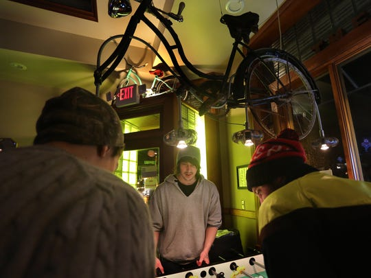 From left, Zachary Schuster, Jameson Stone and Nathaniel Green, all of Wausau, play foosball Thursday at the Glass Hat in Wausau. The tavern has adjusted its focus in the past decade to be a hip venue for artists and young adults.