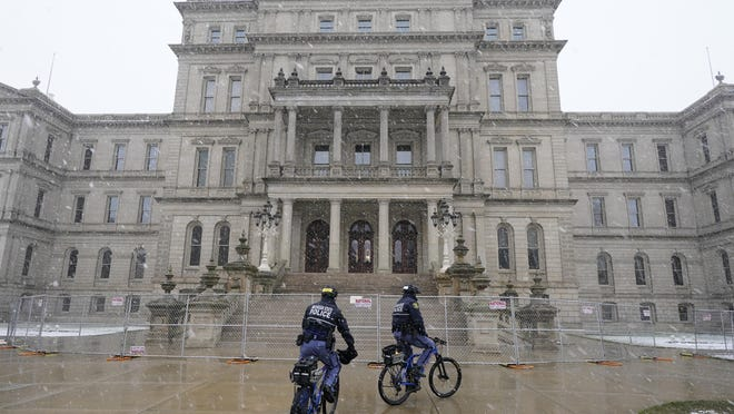 Michigan State Police officers patrol outside the state Capitol in Lansing Friday. Crews also worked on offices across the street from the state Capitol ahead of expected armed protests on Sunday.