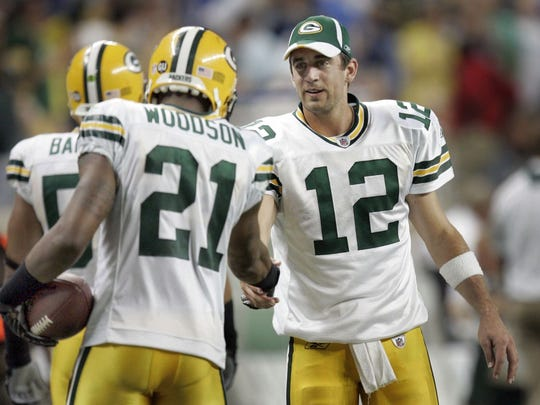 Green Bay Packers' Aaron Rodgers shakes the hand of teammate Charles Woodson after Woodson scored on a 41-yard interception in a 2008 game against the Detroit Lions.