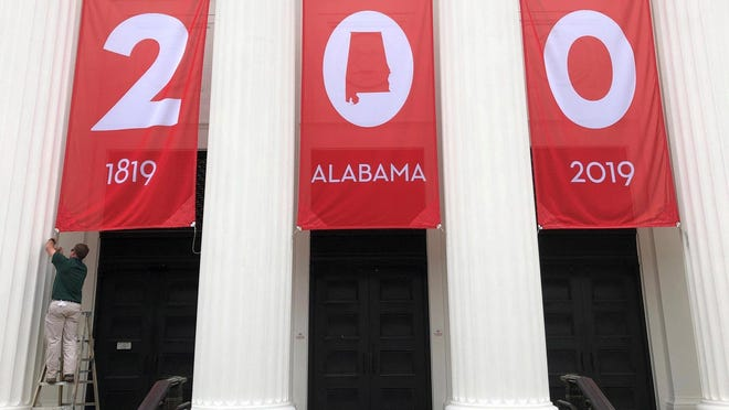 "In this Feb. 28, 2019, photo a worker adjusts a banner celebrating Alabama's bicentennial outside the Department of Archives and History in Montgomery, Ala. Alabama's main state history agency is acknowledging that it helped perpetuate systemic racism by promoting Confederate narratives while ignoring those of Black people, a ""statement of recommitment"" issued Tuesday, June 23, 2020 by the Alabama Department of Archives and History said."
