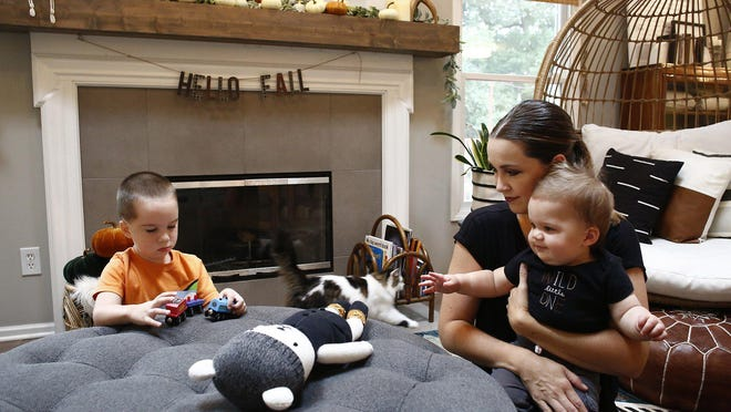 Kelly Pohly left her marketing job in July to stay home with their three sons after the pandemic increased stress about finding child care, working from home and figuring out the boys' schooling. She is seen with sons, Anderson, 3, and Graham, 10 months old, at their Westerville home.