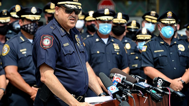 Natick Police Chief James Hicks, who serves as chairman of the Municipal Police Training Committee, speaks at a rally with dozens of police chiefs addressing proposed state police reform bills.  The rally was held at an otherwise empty AMC Movie theatre parking lot Tuesday morning.