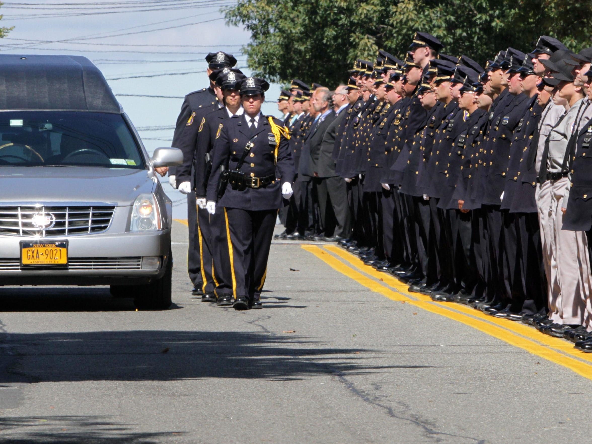 Police stand at attention as the hearse of Yonkers Police Lt.. Roy McLaughlin, 38, passes by after his September funeral. McLaughlin had helped rescue efforts at ground zero after 9/11 and his death, from cancer, was attributed to his work there.