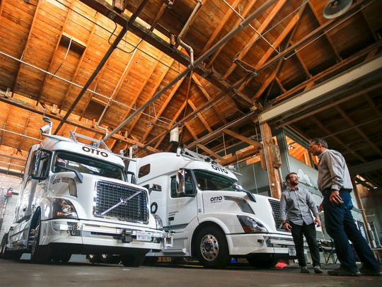 Employees stand next to self-driving, big-rig trucks
