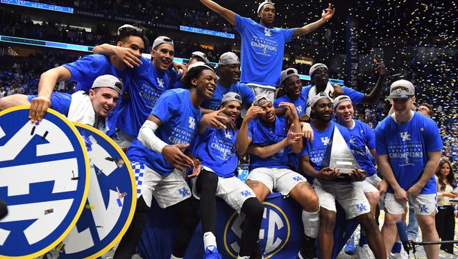 Kentucky Wildcats players celebrate with the championship trophy after a win over Arkansas Razorbacks during the SEC Conference Tournament at Bridgestone Arena on March 12.