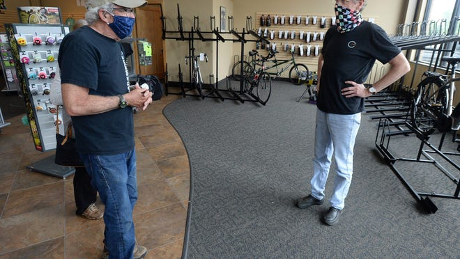 Customer Tom Fetterman, 69, left, talks with Competitive Gear owner Peter McMaster on Wednesday at the bicycle shop in Millcreek Township. Fetterman did not find the type of bike he was looking for and McMaster, 60, described difficulty in getting new bikes in stock due to the COVID-19 coronavirus pandemic.