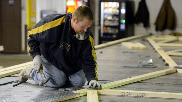 Jeff Strom uses a laser to line up a gusset plate while assembling a roof truss at Component Manufacturing Co. in Sioux Falls. Ag equipment makers and dealers are feeling the effects of a reduction in farm income.