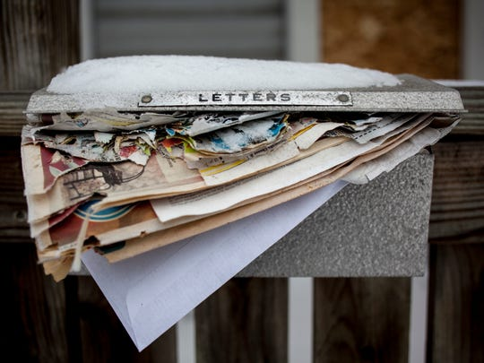 A mailbox is stuffed with faded and torn papers at 230 13th Street in Port Huron. The house is one of many that will be demolished as part of a grant from the Michigan State Housing Development Authority.