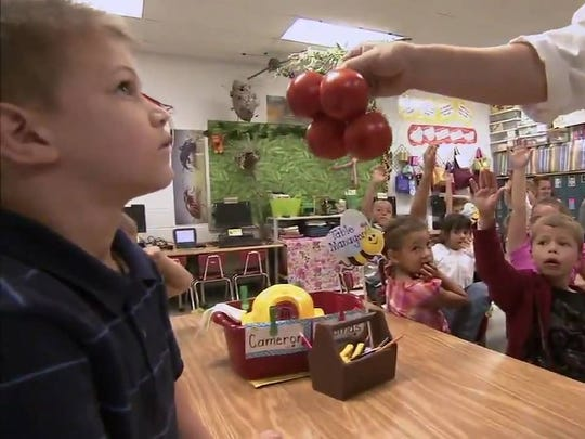 "A child in Huntington, West Virginia, is presented with fresh tomatoes in a 2010 episode of Jamie Oliver's ""Food Revolution,"" which spotlighted childhood obesity in Appalachia."