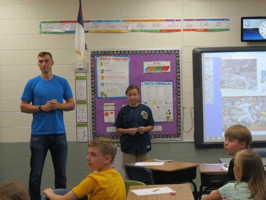 Brewers' pitcher Brent Suter (left) talks to a class of Divine Redeemer students with student Jordan Young (right) at his side. She led him to each of the fifth, sixth, seventh and eighth grade classrooms that he spoke with.