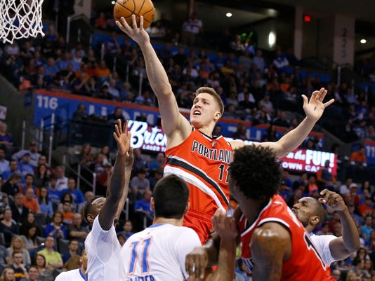 Portland Trail Blazers forward Meyers Leonard, top, shoots over Oklahoma City Thunder guard Anthony Morrow, left, and center Enes Kanter, bottom center, in the second quarter of an NBA basketball game in Oklahoma City, Monday, March 14, 2016. (AP Photo/Sue Ogrocki)