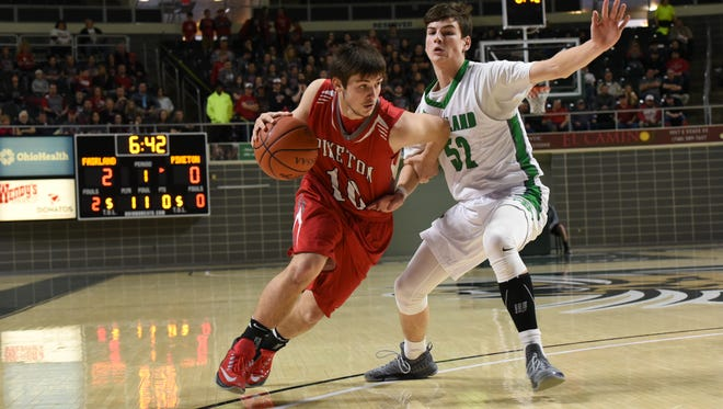 Piketon's Casey Moore drives against Fairland's Gunner Short during the first quarter of Sunday's Division III district semifinal at Ohio University. The Redstreaks fell 74-42.