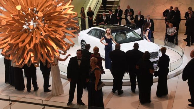 People mingle near the Lincoln Continental at the Charity Preview.