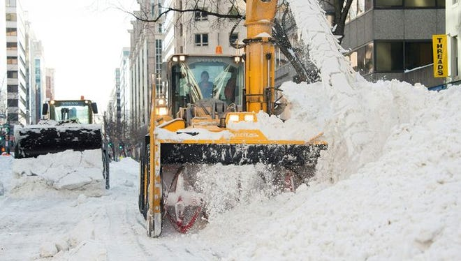 Trucks clear snow from a street in downtown Washington, two days after a massive snowstorm on Jan. 25, 2016.