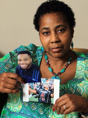 Marilyn Copenhaver Britten holds photos of her son Anton Kirby, 18, who was shot four times in the face by a store clerk during an alleged armed robbery attempt on July 29 at the Harrison Food Mart. The clerk has a license to carry a concealed weapon. Kirby died a few days after the incident.