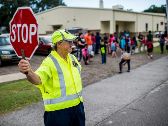 Barbara Breaux, a crossing guard of 39 years, holds