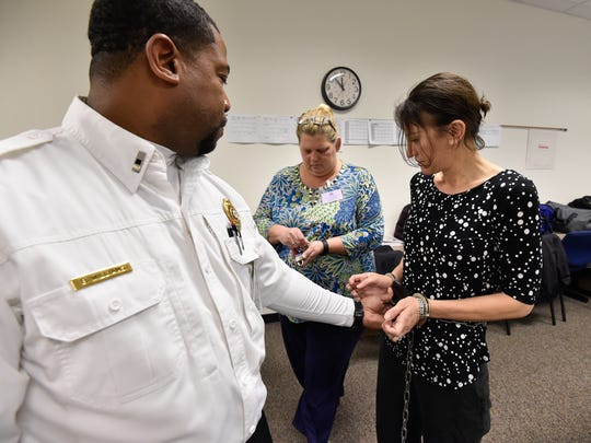 Delaware Department of Correction Staff Lt. Bernell Williams, left, discusses proper handcuffing techniques with correctional counselor Lisa VanHorn, middle, and teacher  Cindy DelGiorno. Teachers in the correctional facility must complete training just like any staff member beginning employment in the state penal system.